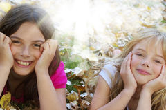 Happy kids. Two happy girls lying down in autumn leaves Stock Photo