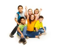 Happy kids. Happy diversity looking boys and girls sitting happy with lifted hands Stock Photography