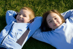 Happy kids. Two happy kids lying on the grass and smiling Stock Photo