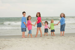 Happy kids. Adorable happy kids holding hands and walking on the beach royalty free stock photos
