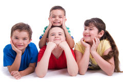 Happy kids. A studio view of four happy, smiling kids lying on the floor.  White background Royalty Free Stock Images