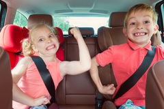 Happy kids, adorable girl with her brother sitting together in m. Odern car locked with safety belts enjoying family vacation trip on summer weekend royalty free stock photography