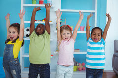 Happy kids with arms raised together. In the bedroom Stock Image