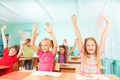 Happy kids with arms up sit in classroom rows Royalty Free Stock Images