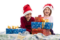 Happy kids in bed with Christmas presents isolated Stock Photography