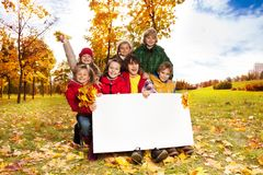 Happy kids with blank placard. Happy smiling group of kids, friends, boys and girls, showing blank placard board to write it on your own text in autumn park with Royalty Free Stock Photo