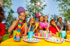 Happy kids blowing whistles at outdoor B-day party Stock Photos