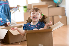 Happy kids with boxes at new home after moving stock image