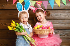 Happy kids boy and girl dressed as Easter bunnies with basket of. Happy kids boy and girl dressed as Easter bunnies laughing with basket of eggs and flowers on Royalty Free Stock Image