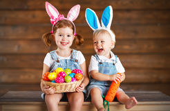 Happy kids boy and girl dressed as Easter bunnies with basket of. Happy kids boy and girl dressed as Easter bunnies laughing with basket of eggs on wooden royalty free stock photography