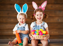 Happy kids boy and girl dressed as Easter bunnies with basket of. Happy kids boy and girl dressed as Easter bunnies laughing with basket of eggs on wooden Stock Images