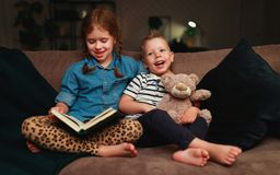 Happy kids boy and girl reading a book in the evening in dark royalty free stock photography