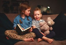 Happy kids boy and girl reading a book in the evening in dark stock photos