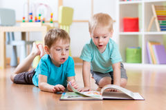 Happy kids boys brothers reading encyclopedia together at home Stock Image