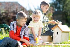 Happy kids boys brothers tinkering outdoors Stock Image