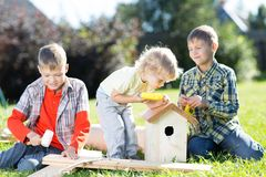 Happy kids boys brothers tinkering outdoors at sunny day Stock Photos