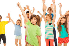 Happy kids boys and girls with lifted hands Stock Photo
