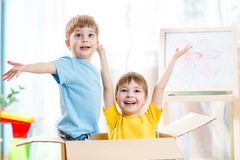 Happy kids boys playing and sitting in cardboard Stock Photos