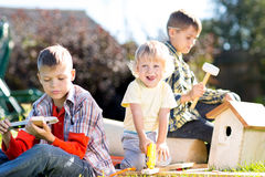 Happy kids brothers making wooden birdhouse by hands Royalty Free Stock Images
