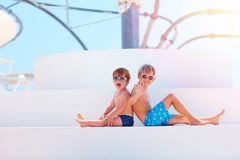 Happy kids, brothers in swimmimg trunks relaxing near the pool royalty free stock photography