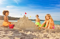 Happy kids building big sand castle on the beach royalty free stock photos