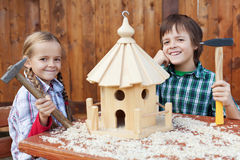 Happy kids building a bird house. Smiling and holding hammers Royalty Free Stock Photo