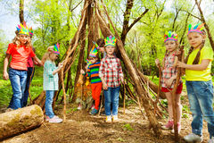 Happy kids building wigwam in the forest. Happy boys and girls in Injun`s headdresses, building wigwam of branches in the forest Stock Image