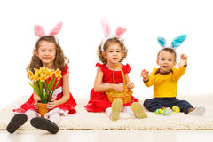 Happy kids with bunny ears. Sitting on carpet and holding easter eggs and flowers Stock Photos