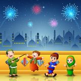 Happy kids celebrate for Eid Mubarak with mosque and fireworks background Stock Image
