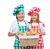 Happy kids with chef hats holding basket with bakery products Royalty Free Stock Photo