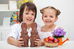 Happy kids with chocolate bunnies. Happy kids smiling and holding chocolate easter bunnies Royalty Free Stock Image