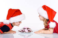 Happy kids with christmas cookies. Happy kids leaning over a plate full of christmas cookies - isolated Royalty Free Stock Image