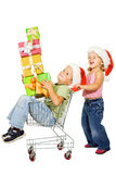 Happy kids christmas shopping. Happy kids with shopping cart and christmas presents - isolated Stock Image