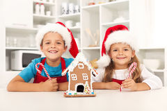 Happy kids at christmas time in the kitchen. With their gingerbread house Stock Photos