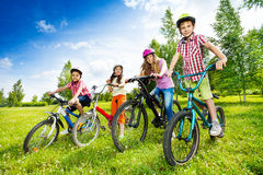 Happy kids in colorful bike helmets holding bikes Stock Photography