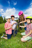 Happy kids in colorful helmets repair bike Royalty Free Stock Image