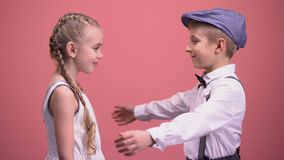 Happy kids couple hugging and looking to camera, isolated on pink background stock footage