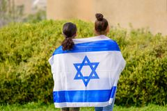Happy kids, cute little teen girls with Israel flag. Two patriot jewish teenager girl standing and enjoying with the flag of Israel on nature background royalty free stock photos