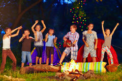 Happy kids dancing around campfire royalty free stock photos
