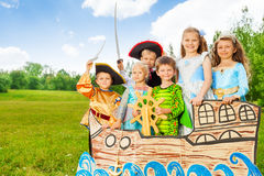 Happy kids in different costumes stand on ship. Together and smile Royalty Free Stock Images