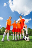 Happy kids of different height with football Stock Image