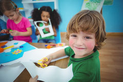 Happy kids doing arts and crafts together. At their desk Royalty Free Stock Image