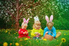 Happy kids on easter eggs hunt in spring. Nature stock photography