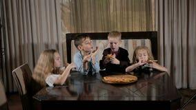 Happy kids eat pizza in the restaurant stock video