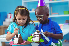 Happy kids eating birthday cake Stock Photography