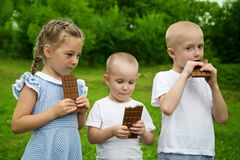 Happy kids eating chocolate. Outdoors Royalty Free Stock Image