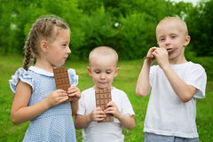 Happy kids eating chocolate. Outdoors in summer park Royalty Free Stock Photo