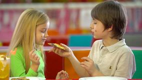 Happy kids eating chocolate pizza during dinner at entertainment center. Happy kids eating chocolate pizza during dinner at entertainment center on vacation stock footage
