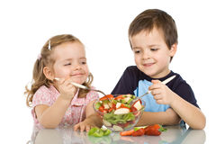 Happy kids eating fruit salad Stock Images