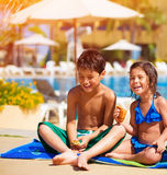 Happy kids eating near pool. Two happy kids eating croissant near pool, having breakfast on the beach, active summer holidays, brother and sister enjoying sunny Stock Images